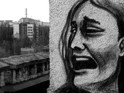 Murales a Chernobyl, sullo sfondo la ciminiera della centrale nucleare